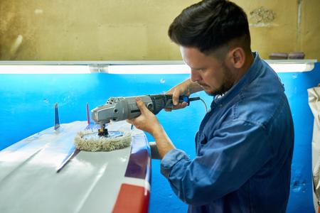 Man Polishing Custom Surfing Board