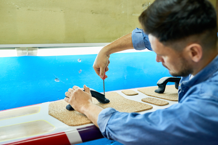 Back view portrait of handsome modern man  making custom  surfing board placing pads on it and screwing in handles 版權商用圖片