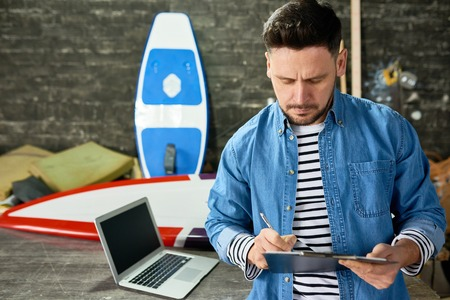 Handsome Man Writing on Clipboard in Custom Surfing Boards Shop Banco de Imagens