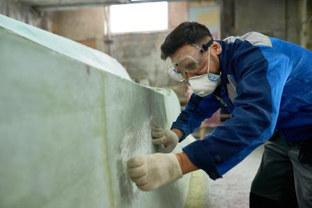 Man Repairing Yachts in Workshop