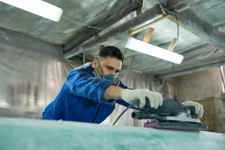 Worker Polishing Motorboat in Workshop