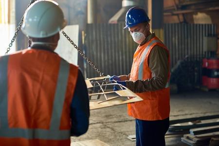 Fabrieksarbeiders die Hijsbalk gebruiken Stockfoto