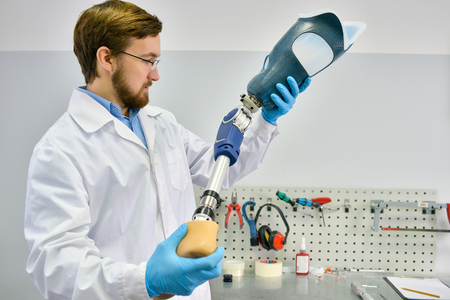 Young Prosthetist Holding  Artificial Leg Stock Photo