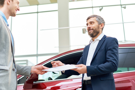 Handsome Car Salesman Giving Contract to Client