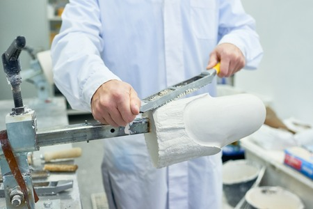 Prosthetist Shaping Leg Molds in Laboratory 写真素材
