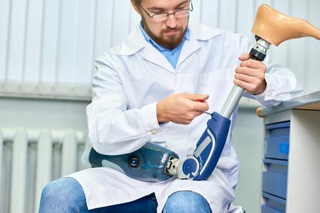Bebaarde arts die prothetisch been assembleert