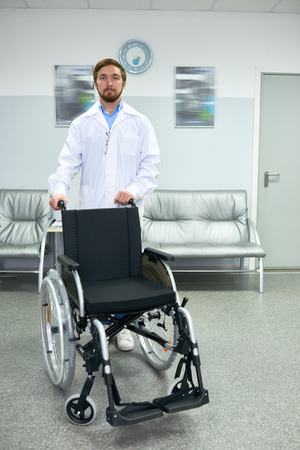 Doctor Posing with Empty Wheelchair Stock Photo