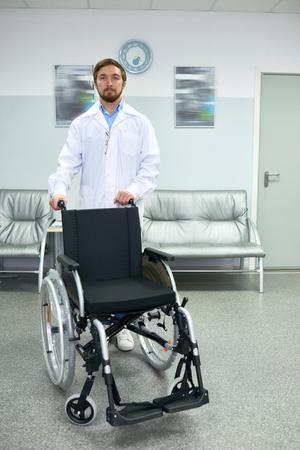 Doctor Posing with Empty Wheelchair Stock fotó