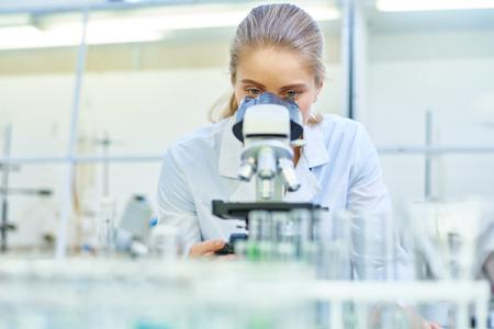 Weiblicher Wissenschaftler , der Mikroskop im Labor verwendet Standard-Bild