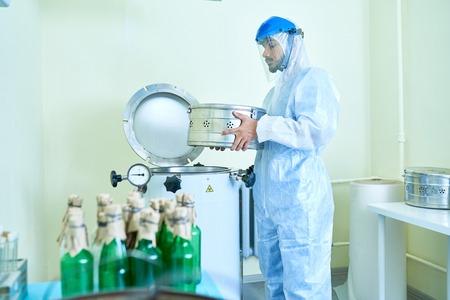 研究室で機械を操作する科学者