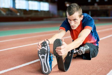 Handicapped Sportsman Stretching in Stadium
