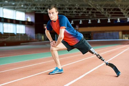 Disabled  Runner Stretching in Stadium Stockfoto
