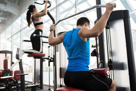 Vista lateral de dos personas que se ejercitan en las máquinas en un gimnasio moderno por ventana Foto de archivo - 94299079