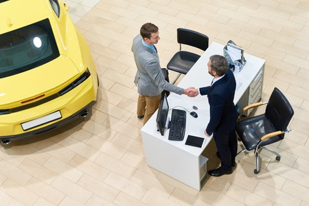 Successful Man Buying Car in Showroom