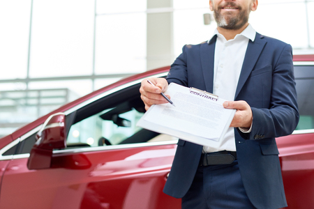 Car Salesman Giving Contract to Client Stockfoto