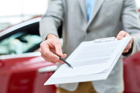 Close up view  portrait of unrecognizable car salesman handing purchase contract to client buying brand new car in luxury showroom Stockfoto