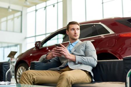 Handsome Man Waiting in Car Showroom Stockfoto