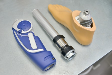 High angle background of disassembled prosthetic leg and foot on table in orthopedic equipment shop, disability concept