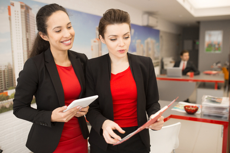 Two Businesswomen Discussing Work in Office Stock Photo