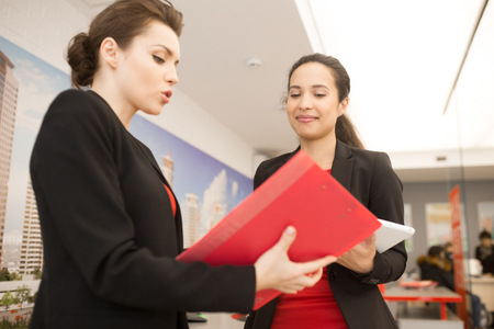 Two Women Discussing Work in Office Stock Photo