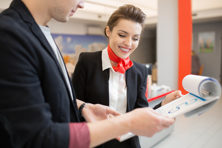 Portrait of beautiful young woman wearing black and red uniform talking to client in bank holding clipboard