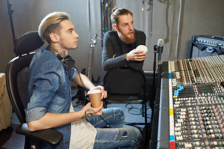 Sound engineers with coffee working in recording studio Stock Photo