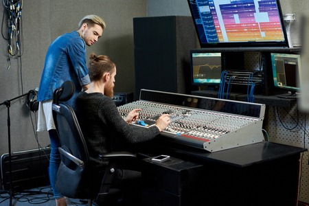 Audio engineer choosing sounds for track together with musician Stock Photo