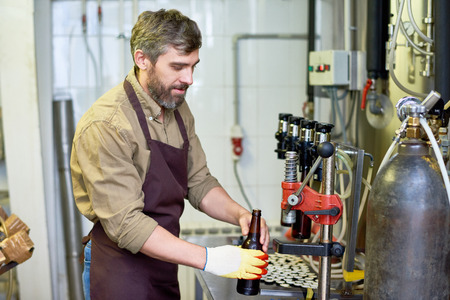 Content handsome technician putting beer in bottles at factory 写真素材