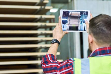 デジタルタブレットを介して写真を撮る労働者