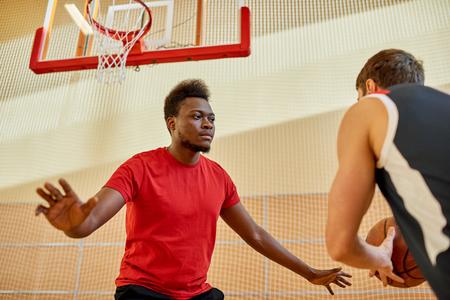 African man playing defense in basketball Stok Fotoğraf
