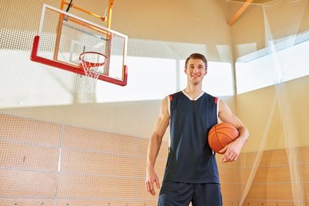 Portrait of happy handsome tall basketball player on court Banque d'images