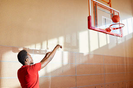 Skilled young basketball player training on court