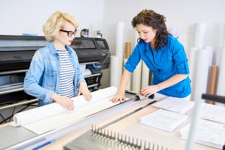 印刷店で紙を切る女性