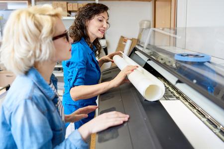 印刷機で紙を交換する女性 写真素材
