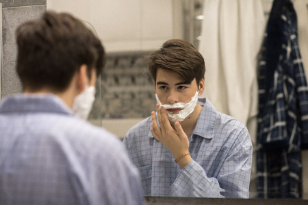 Young Man Shaving for First Time