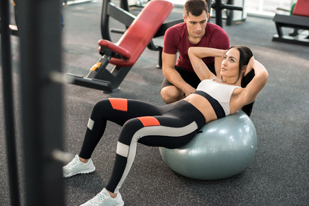 Fitness Instructor Helping Woman in Health Club Stock Photo