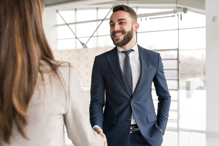Smiling Car Salesman Shaking Hands with Client Stockfoto