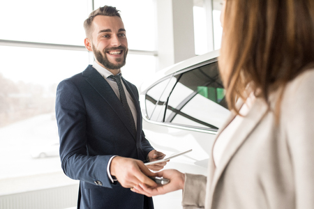Handsome Car Salesman Giving Keys to Client