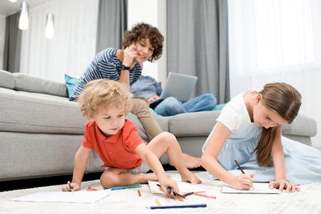 自宅で子供たちを見ている母親