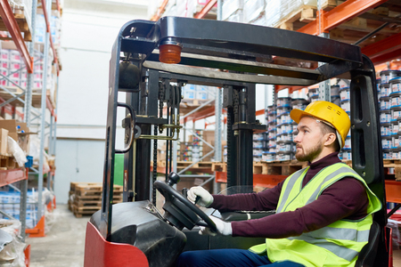 Side view portrait of young warehouse worker sitting inside forklift moving goods from tall storage shelves, copy space