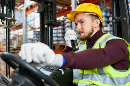 Waist up portrait of young man sitting in forklift and using walkie-talkie while moving goods in warehouse, copy space Stockfoto