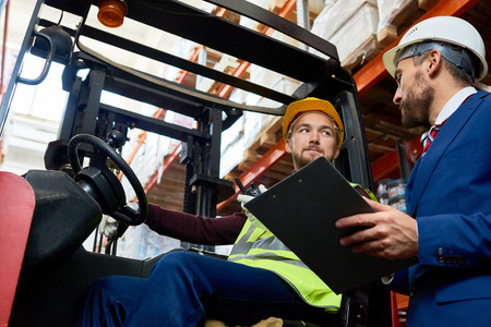 Low angle portrait of mature businessman talking to warehouse worker sitting in forklift car, copy space Stockfoto