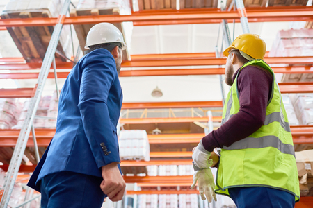 Back view low angle portrait of warehouse manager and factory worker looking up at tall storage shelves in warehouse