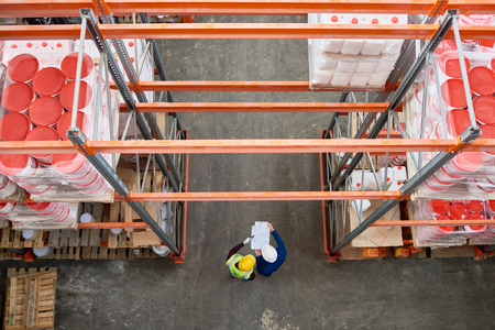 Top view background image of tall shelf rows in modern warehouse with two people wearing hardhats standing in aisle