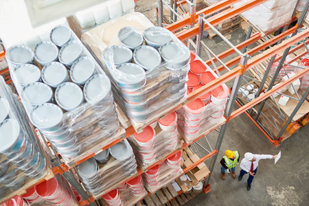 Top view background image of tall shelves in modern warehouse with two workers wearing hardhats standing in aisle