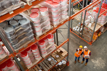 High angle  background image of tall shelves in modern warehouse with two workers wearing hardhats standing in aisle pointing up, copy space Reklamní fotografie