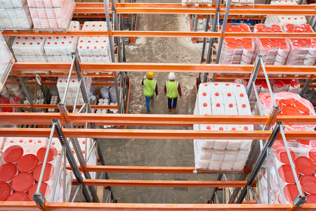 Top view background image of tall shelves in modern warehouse with two workers wearing hardhats walking in aisle, copy space