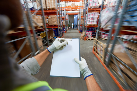 High angle close up of workers hands holding clipboard with documentation standing in modern warehouse, copy space