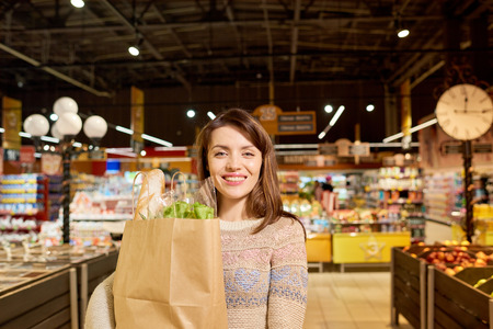 Portrait of charming  young woman smiling cheerfully at camera holding paper bag with groceries while shopping in supermarket, copy space