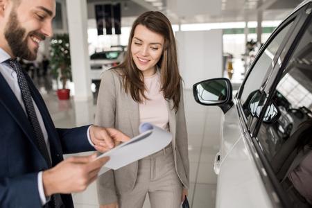 Beautiful Woman Talking to Salesman in Car Showroom